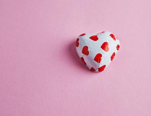 Valentijnsdag snoep harten op roze tafel.