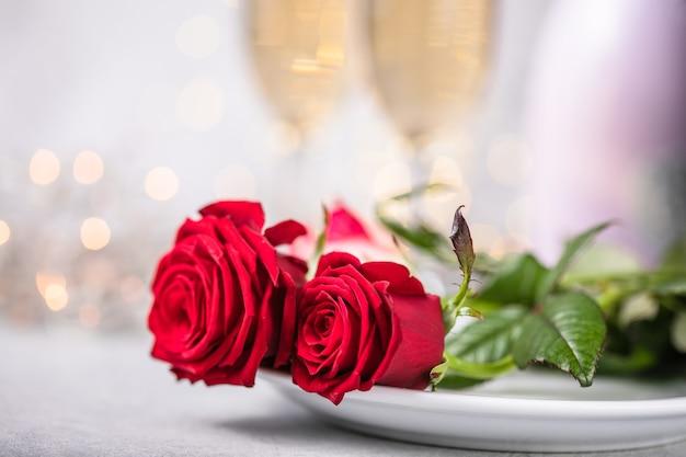 Valentijnsdag tabel met rode rozen en champagneglazen op concrete achtergrond. valentijnsdag wenskaart - afbeelding
