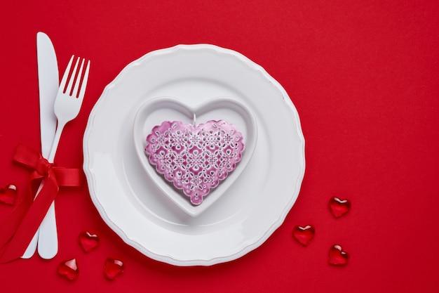 Valentijnsdag tafel of concept met lege roze plaat en whiteware op dieprode of rode tafel. bovenaanzicht plat lag met kopie ruimte.
