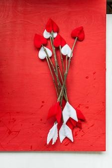 Valentijnsdag takje pijlen op rode houten achtergrond. handgemaakte cupid's pijlen.