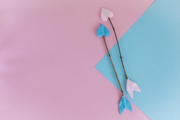 Valentijnsdag takje pijlen op roze en blauwe achtergrond