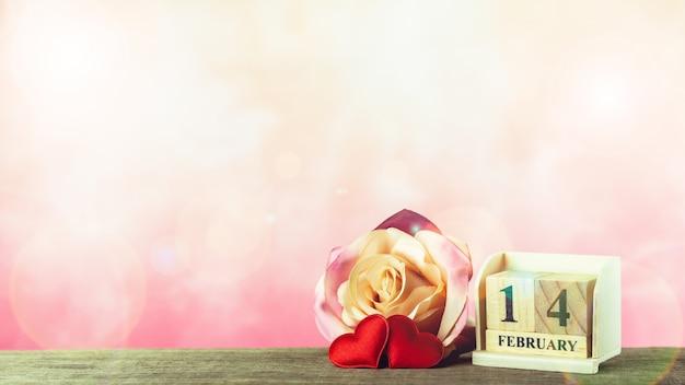 Valentijnsdag thema met houten blok kalender en rode harten. - 14 februari.