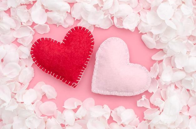 Valentijnsdag, twee harten op een roze achtergrond met witte bloemblaadjes van appelboom bloemen
