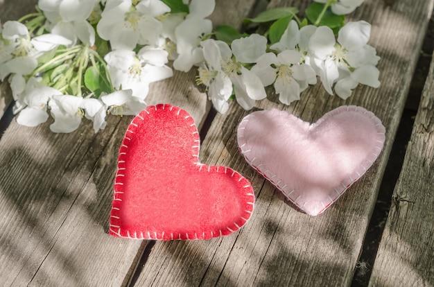 Valentijnsdag, twee harten op houten tafel met appelboom bloemen met zonnestralen