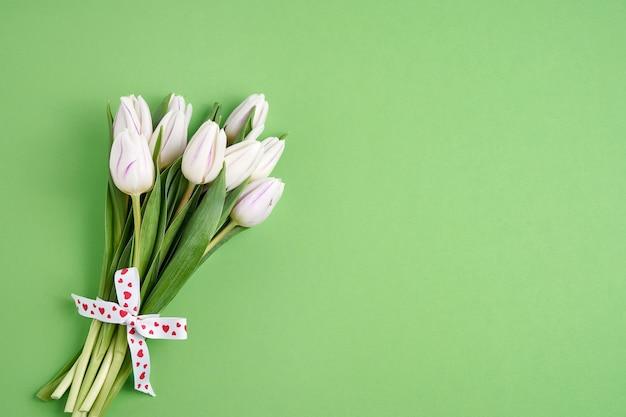 Valentijnsdag, verjaardag concept. wit tulpenboeket dat met hartenlint wordt verfraaid op groene achtergrond. ruimte kopiëren, bovenaanzicht