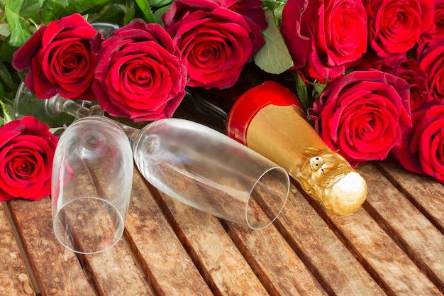 Valentijnsdag verse donkerrode rozen en paar glazen met hals van champagne wijn
