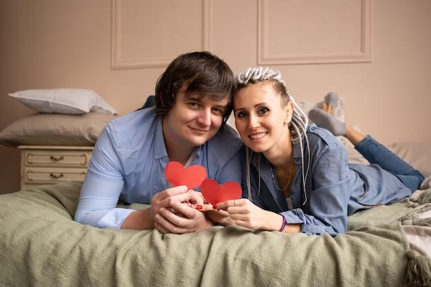 Valentijnsdag vieren. man en vrouw die thuis met rood hartvalentijnskaart in handen kussen.