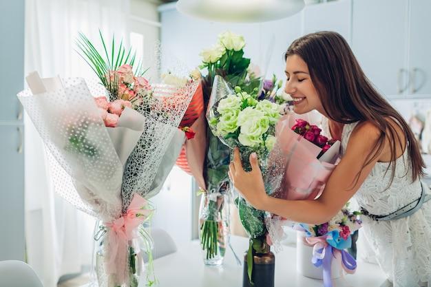 Valentijnsdag, vrouwendag. vrouw vond veel boeketten bloemen op keuken. gelukkig meisje ruikende rozen