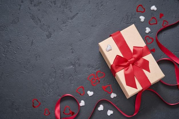 Valentijnsdag wenskaart. geschenkdoos met rood lint en hart beeldjes op zwarte achtergrond bovenaanzicht.