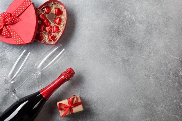 Valentijnsdag wenskaart met champagneglazen en snoep harten op stenen achtergrond.