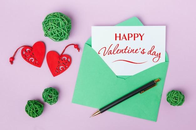 Valentijnsdag wenskaart met envelop en harten op roze tafel