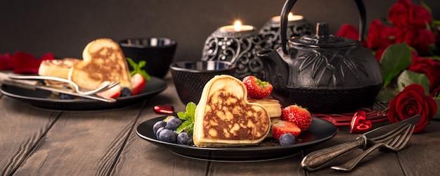 Valentijnsdag wenskaart met heerlijke pannenkoeken in de vorm van hart, groene thee, zwarte theepot, kaarsen en rozen. valentijnsdag concept. kopieer ruimte. banner