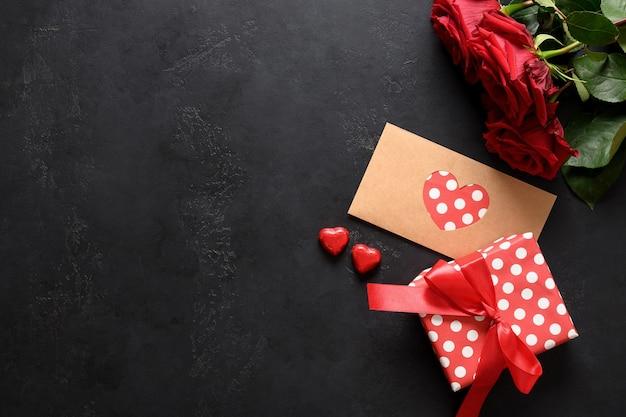 Valentijnsdag wenskaart met liefdesbrief in decoratieve envelop, rode rozen en cadeau op zwart met kopie ruimte.