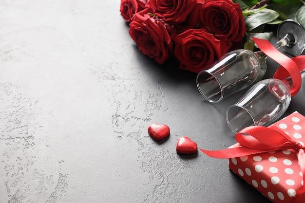 Valentijnsdag wenskaart met rode rozen, wijnglazen en cadeau op zwart met kopie ruimte. detailopname.