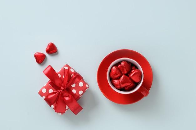 Valentijnsdag wenskaart met rood hart snoep, cadeau en beker