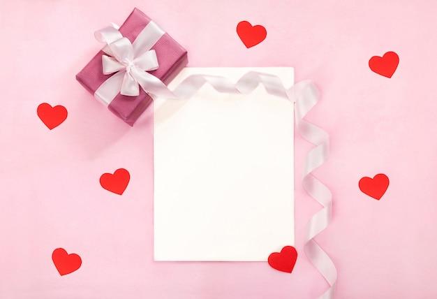 Valentijnsdag wenskaart met roze geschenkdoos, witte strik, lang gebogen lint en papieren rode harten