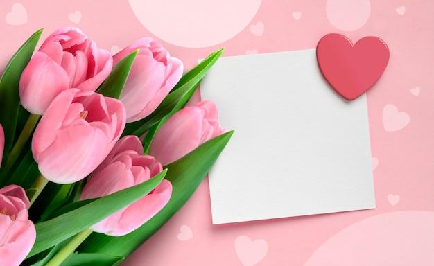 Valentijnsdag wenskaart met roze tulpen en blanco papier notitie met hart op roze achtergrond.