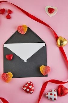 Valentijnsdag wenskaart met snoep harten en rood lint op roze achtergrond.