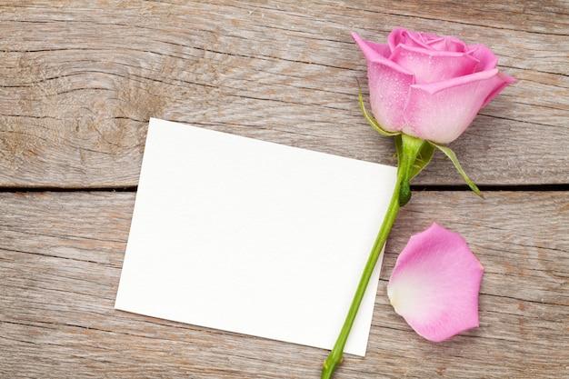 Valentijnsdag wenskaart of fotolijstjes en roze roos over houten tafel. bovenaanzicht met kopieerruimte