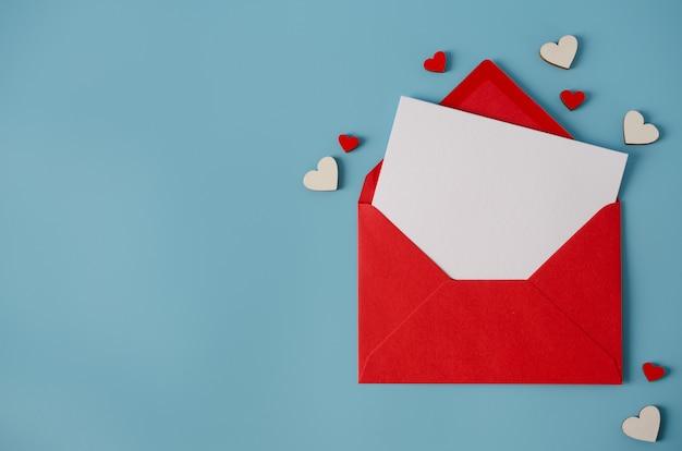 Valentijnsdag wenskaart. rode envelop met lege kaart op blauwe achtergrond.