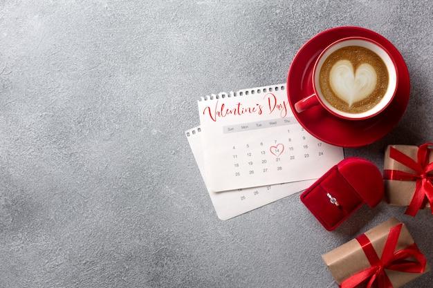 Valentijnsdag wenskaart. rode koffiekop, ring en geschenkdoos over februari kalender. uitzicht van boven