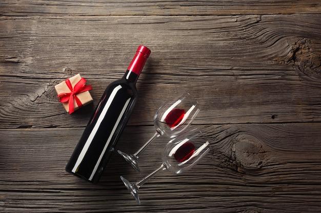 Valentijnsdag wenskaart. rode wijn, geschenkdoos en glazen op houten tafel. bekijk met ruimte voor uw groeten.