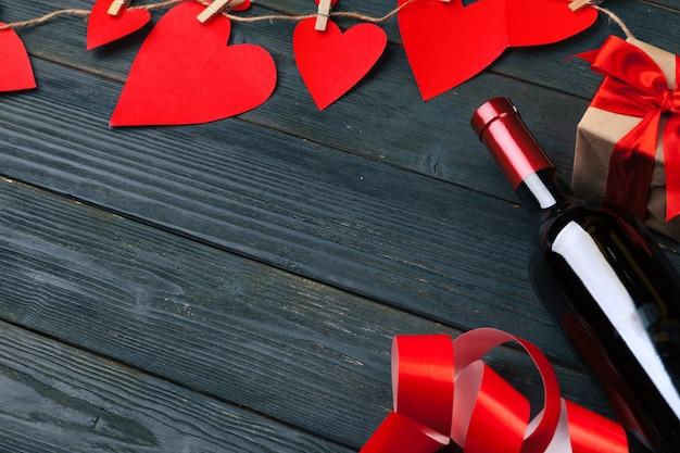 Valentijnsdag wenskaart. rood roze bloemen, wijn en geschenkdoos op houten tafel.