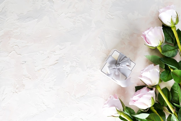 Valentijnsdag wenskaart. roze rozen en geschenkdoos op lichte steen, bovenaanzicht met copyspace