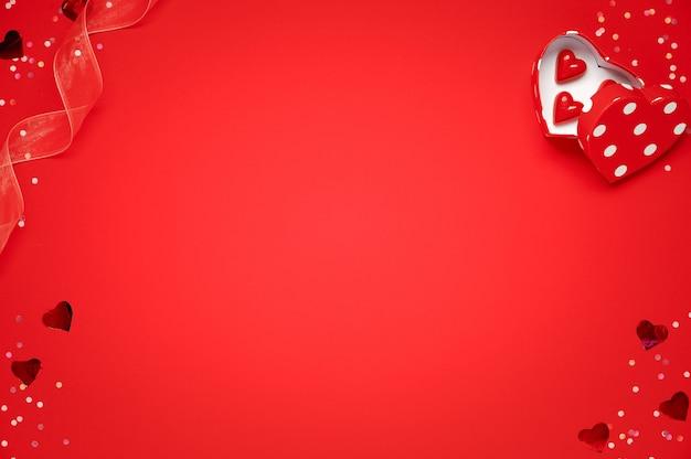 Valentijnsdag wenskaartsjabloon. geschenkdozen, hartdecor en suikergoedsnoepjes over rood.