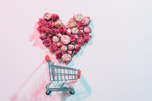 Valentijnsdag winkelen. bloem liefde vormige hart vallen in lege trolley. roze