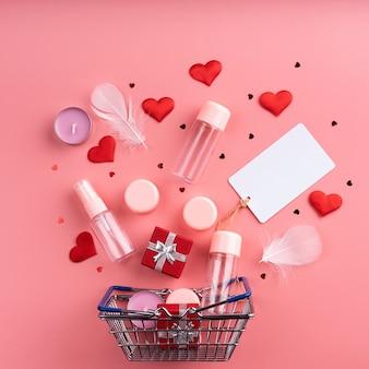 Valentijnsdag winkelen. winkelmandje met verschillende cosmetica, prijskaartje, confetti bovenaanzicht plat lag op roze achtergrond