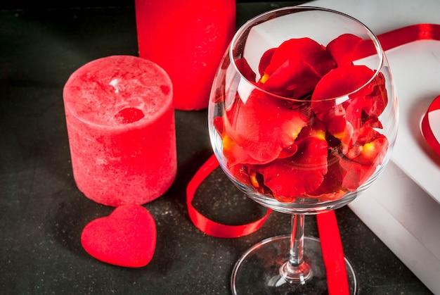 Valentijnsdag, witte verpakte geschenkdoos met rood lint, roze bloemblaadjes in wijnglas, met rode kaars, op donkere steen, copyspace