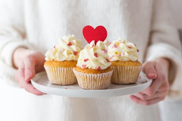 Valentijnsdag. zoet geschenk. vrouwenhanden die een plaat met cupcakes houden die met harten wordt verfraaid