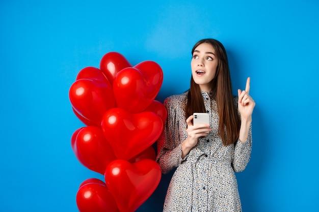 Valentijnsdagbeeld van een romantisch meisje dat een idee werpt na het gebruik van een mobiele telefoon die de vinger opsteekt en...