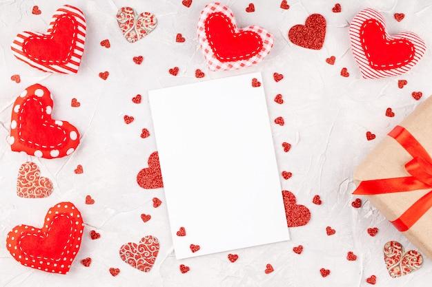 Valentijnsdagdecoratie met harten, geschenkdoos met rood lint en lege kaart