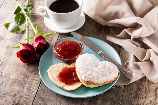 Valentijnsdagontbijt met koffie hartvormig broodje en bessenjam