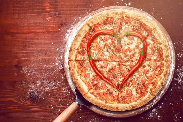 Valentijnsdagpizza met peper die bovenop een pizza wordt gelegd