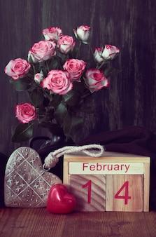 Valentijnsdagstilleven met houten kalender, roze rozen en h
