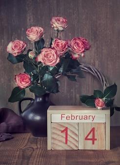Valentijnsdagstilleven met houten kalender, roze rozen en harten op donker