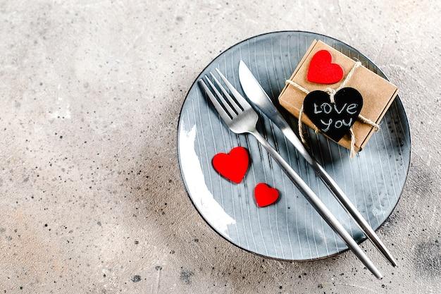 Valentijnsdagtafel met geschenkdoos, bestek en rode harten op een bord op lichte marmeren achtergrond
