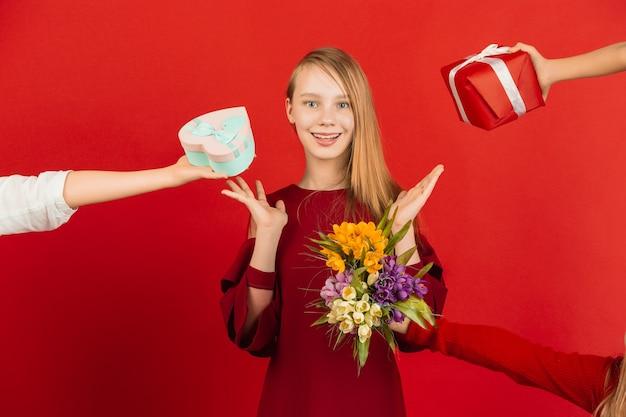 Valentijnsdagviering. gelukkig, leuk kaukasisch meisje dat op rode studioachtergrond wordt geïsoleerd.