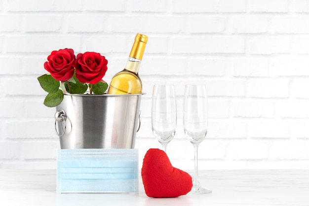 Valentijnsdagviering met beschermingsconcept voor wijn, boeket en gezichtsmasker tijdens deze moeilijke tijd.