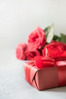 Valentijnskaartenkaart met rode giftdoos, boeketrozen op wit.