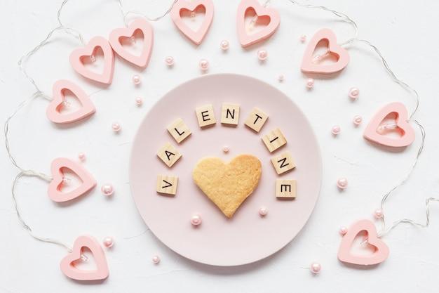 Valentijnskaartwoord en hartvormig koekje op een plaat