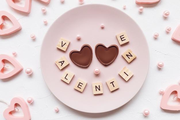 Valentijnskaartwoord en twee chocoladeharten op een plaat