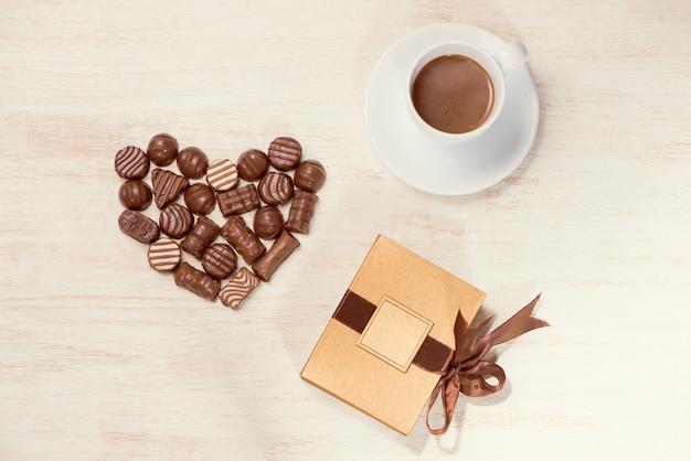 Valentine achtergrond met chocolade truffels en koffiekopje.