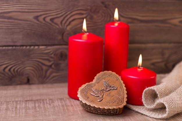 Valentine achtergrond rode kaarsen een doos in de vorm van een hart in rustieke stijl selectieve aandacht kopieer de ruimte
