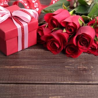 Valentine-achtergrond van giftdoos en rode rozen op hout