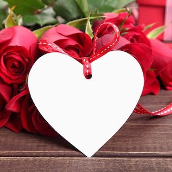 Valentine-achtergrond van witte giftmarkering en rode rozen op hout