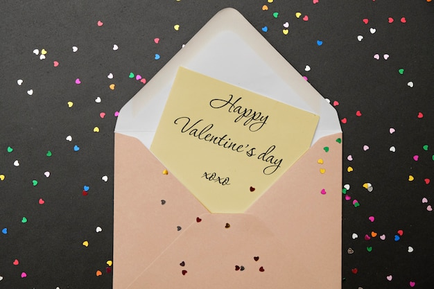 Valentine-dag: envelop met harten en tekst i love you op zwarte achtergrond en confetti